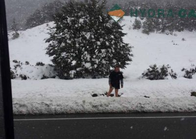 worker in snow on the side of the road in the south island of new zealand