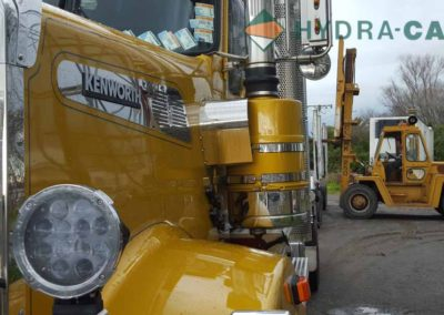 Kenworth truck with a forklift in background