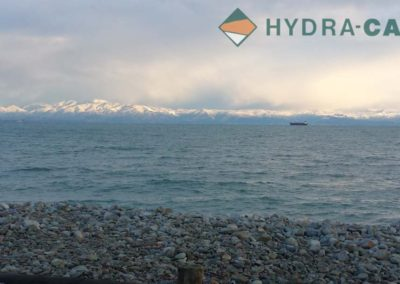 container barge on sea in front of snow capped mountains in new zealand